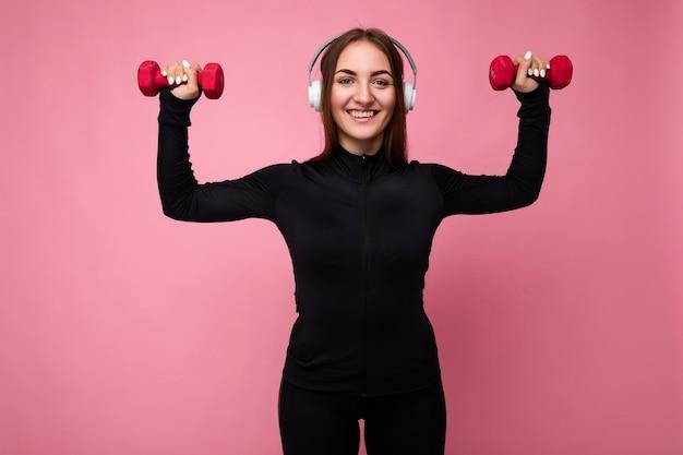 Belle jeune femme brune souriante et positive portant des vêtements de sport noirs isolés sur rose