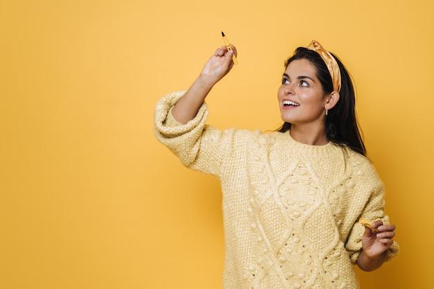 Belle jeune femme brune en vêtements jaunes tenant un stylo, écrivant en l'air, se prépare à l'examen. concept de mode de vie des personnes.