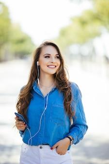 Belle jeune femme brune vêtue d'une robe et marchant dans la rue