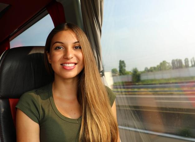 Belle jeune femme en bus souriant à la caméra