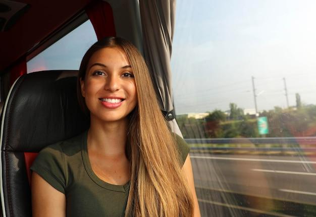 Belle jeune femme en bus sourire à la caméra