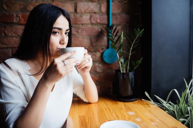 Belle jeune femme buvant du café au café-bar.