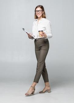 Belle jeune femme buvant du café tenant le presse-papiers posant isolé sur mur blanc
