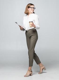 Belle jeune femme buvant du café tenant le presse-papiers posant isolé sur mur de mur blanc