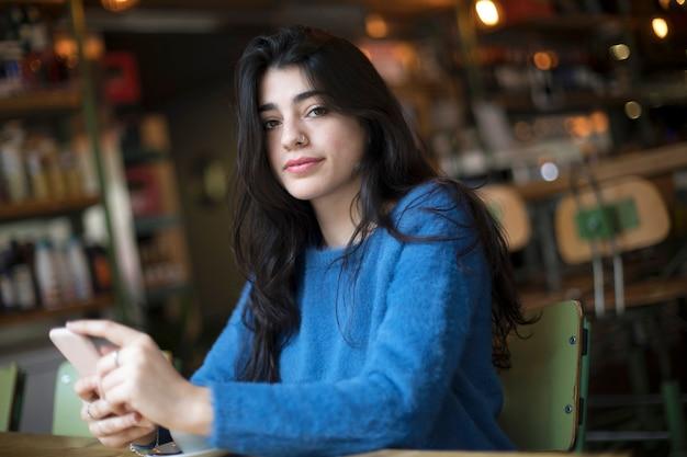 Belle jeune femme buvant du café et utilise son smartphone assis à l'intérieur d'un café urbain. style de vie de ville de café. portrait occasionnel de belle fille