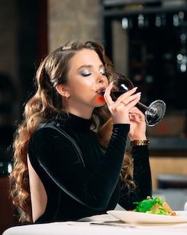 Belle jeune femme buvant du vin dans un restaurant.