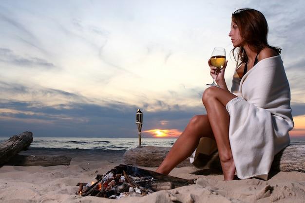 Belle jeune femme buvant du vin sur la plage