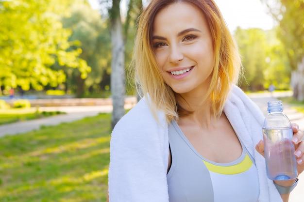 Belle jeune femme buvant de l'eau pendant le jogging matinal dans le parc