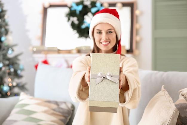 Belle jeune femme avec un cadeau de noël à la maison