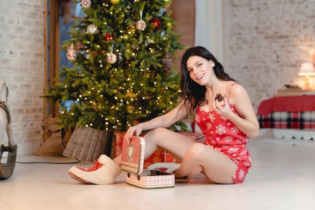 Belle jeune femme avec des cadeaux sur l'arbre de noël