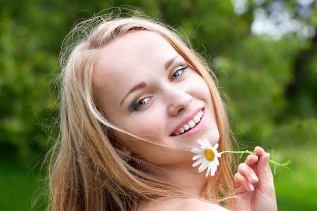 Belle jeune femme à la camomille, jour d'été