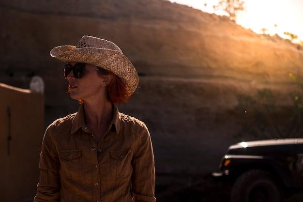 Belle jeune femme à la campagne avec rétro-éclairage doré du coucher du soleil. vivre différemment pour un concept de style de vie heureux.