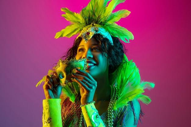 Belle Jeune Femme En Carnaval, Costume De Mascarade élégant Avec Des Plumes Dansant Sur Un Mur Dégradé En Néon Photo gratuit