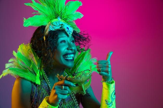 Belle jeune femme en carnaval, costume de mascarade élégant avec des plumes dansant sur un mur dégradé en néon
