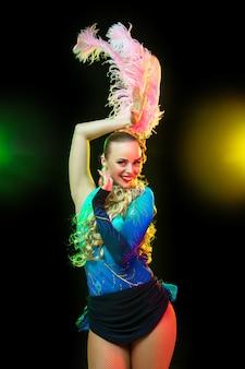 Belle jeune femme en carnaval, élégant costume de mascarade avec des plumes sur un mur noir en néon
