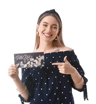 Belle jeune femme avec carte-cadeau sur blanc