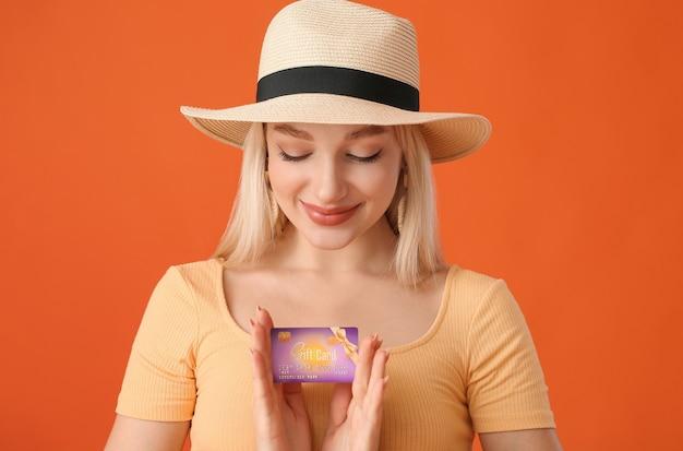 Belle jeune femme avec carte-cadeau sur fond de couleur