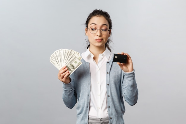 Belle jeune femme avec carte de crédit noire et argent comptant