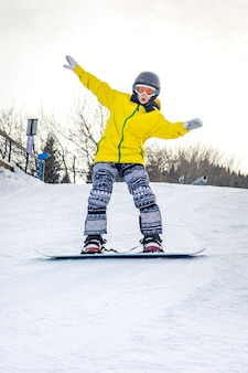 Belle jeune femme en casque noir et veste jaune apprend à faire du snowboard