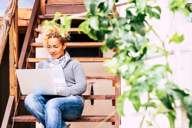 Belle jeune femme caucasienne d'âge moyen travaillant à l'ordinateur portable connecté à internet à l'extérieur de la maison s'asseoir sur un escalier en bois