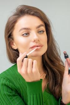 Belle jeune femme caucasienne, appliquer le brillant sur les lèvres en regardant dans le miroir