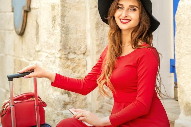 Belle jeune femme caucasienne au chapeau noir souriant et assis dans les escaliers à la porte à l'extérieur.