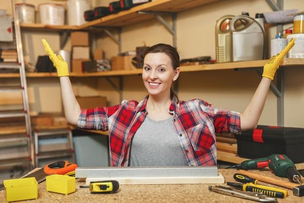 Belle jeune femme caucasienne aux cheveux bruns en chemise à carreaux, t-shirt gris, gants jaunes écartant les mains, travaillant dans un atelier de menuiserie sur une table en bois avec un morceau de fer et de bois, différents outils