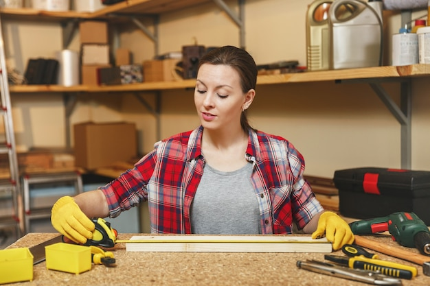 Belle jeune femme caucasienne aux cheveux bruns en chemise à carreaux, t-shirt gris, gants jaunes travaillant dans un atelier de menuiserie sur une table en bois avec différents outils, mesurant la longueur de la barre par un ruban à mesurer