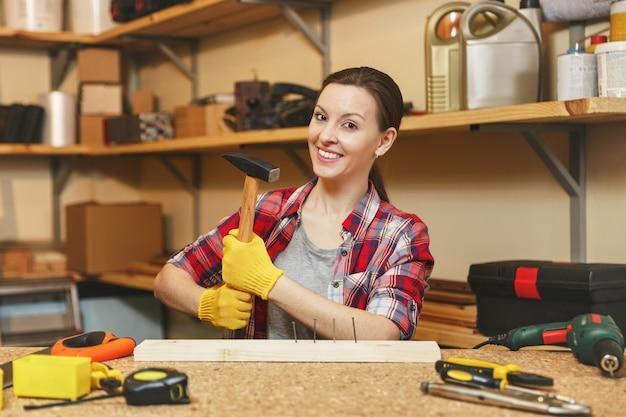 Belle jeune femme caucasienne aux cheveux bruns en chemise à carreaux, t-shirt gris, gants jaunes travaillant dans un atelier de menuiserie sur une table en bois avec un morceau de fer et de bois, différents outils. clou martelé.
