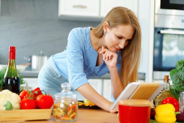 Belle jeune femme caucasienne cuisine et à l'aide de sa tablette numérique dans la cuisine
