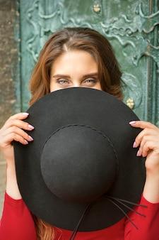Une belle jeune femme caucasienne à la mode se cachant le visage avec un chapeau noir rond