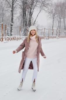 Belle jeune femme caucasienne, patinage sur glace sur la patinoire