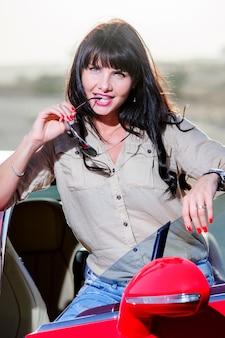 Belle jeune femme caucasienne posant dans le désert, s'amuser, journée ensoleillée dans le désert des emirats arabes unis.