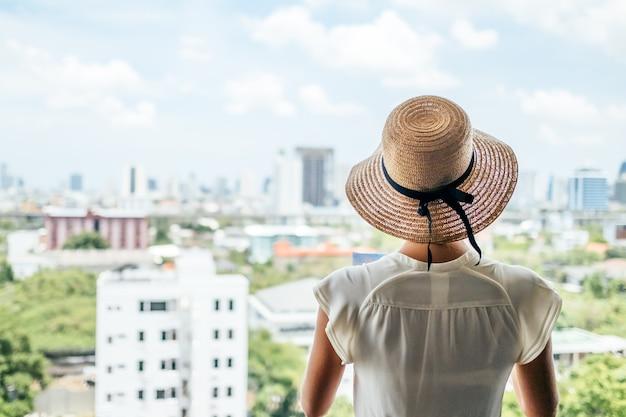 Belle jeune femme caucasienne regardant la ville depuis les hauteurs