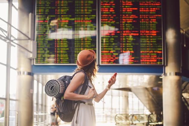 Belle jeune femme caucasienne en robe et sac à dos, debout à l'intérieur de la gare