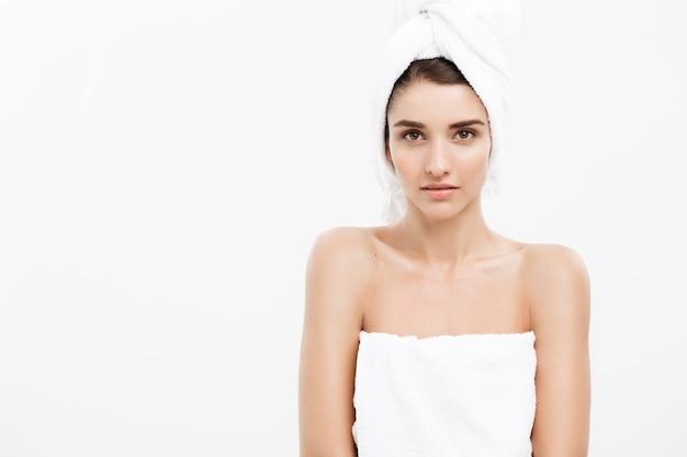 Belle jeune femme caucasienne avec une serviette de bain sur la tête couvrant ses seins, sur blanc