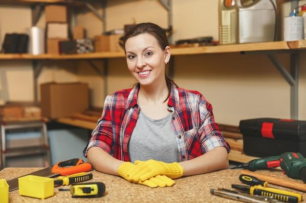 Belle jeune femme caucasienne souriante aux cheveux bruns en chemise à carreaux, t-shirt gris, gants jaunes travaillant dans un atelier de menuiserie sur une table en bois avec différents outils de travail pour hommes. égalité des genres.