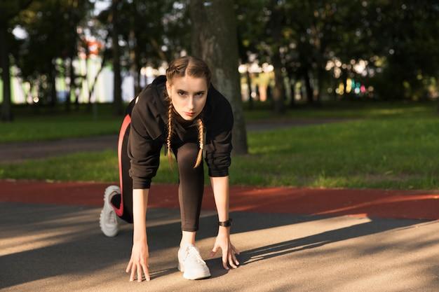Belle jeune femme caucasienne en vêtements de fitness dans un parc.
