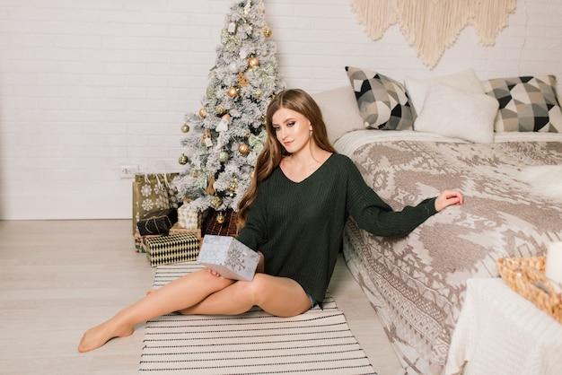 Belle jeune femme célébrant noël à la maison, s'amusant tout en ouvrant des cadeaux