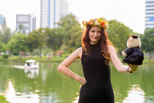 Belle jeune femme célébrant la remise des diplômes au parc