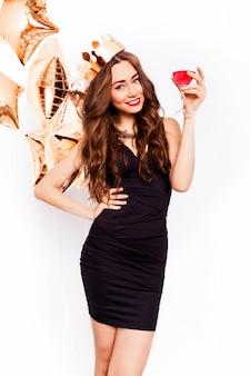 Belle jeune femme célébrant en robe noire sourire et posant avec un cocktail à la main et des ballons de pureté. portrait isolé sur fond de studio.