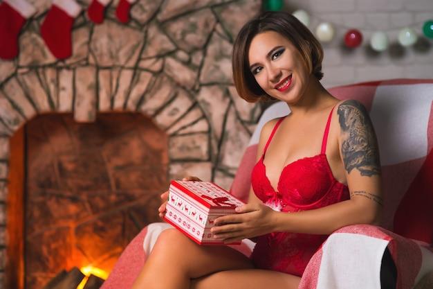 Belle jeune femme célèbre noël à la maison à l'intérieur avec un arbre de noël, des cadeaux, une cheminée, dans un chapeau de père noël
