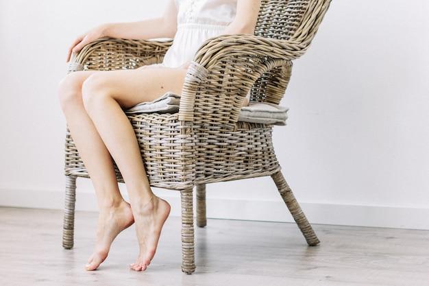 Belle jeune femme en chaise de paille.