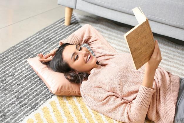 Belle jeune femme en chandail chaud lisant un livre à la maison