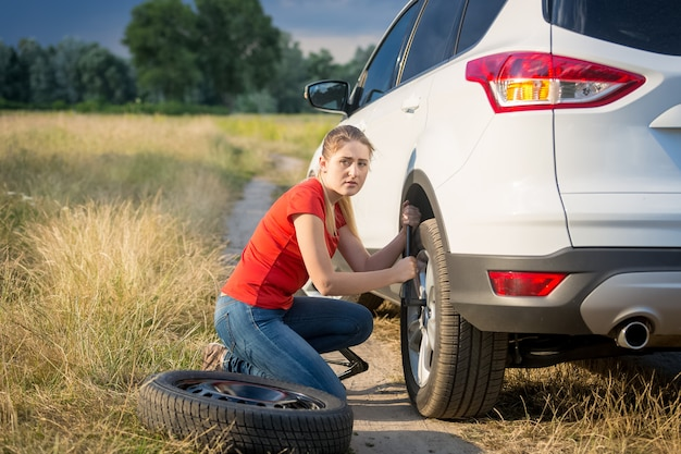Belle jeune femme changeant la roue de voiture sur la route rurale passant par le champ