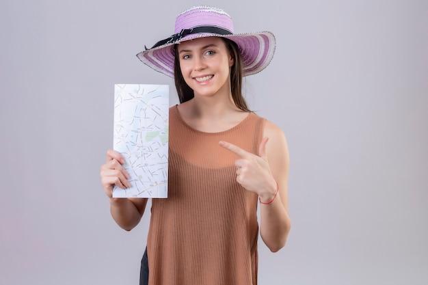 Belle jeune femme en chapeau d'été tenant la carte pointant vers elle souriant avec un visage heureux debout sur fond blanc