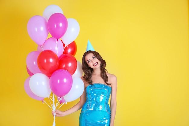 Belle jeune femme en chapeau de fête avec des ballons à air sur jaune