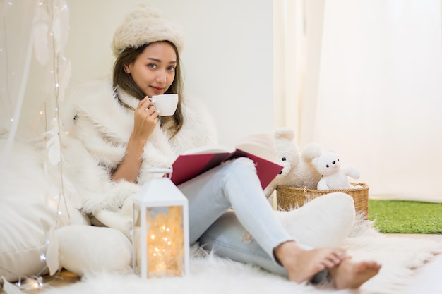 Belle jeune femme avec un chapeau de fourrure blanche et un chandail lit un livre et boit du café ou du thé chaud dans la maison en hiver. une fille souriante célèbre les vacances de noël à la maison.