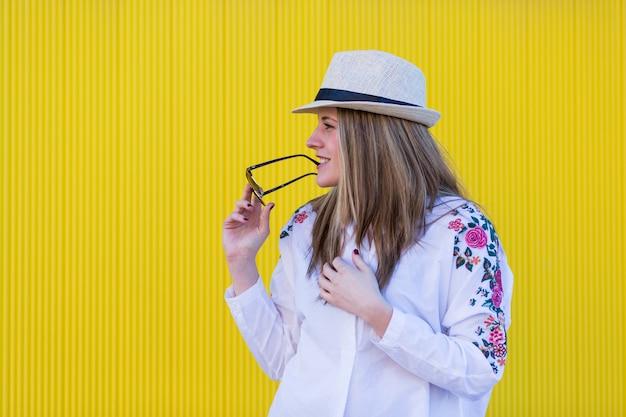 Belle jeune femme avec chapeau et lunettes de soleil s'amuser mur jaune