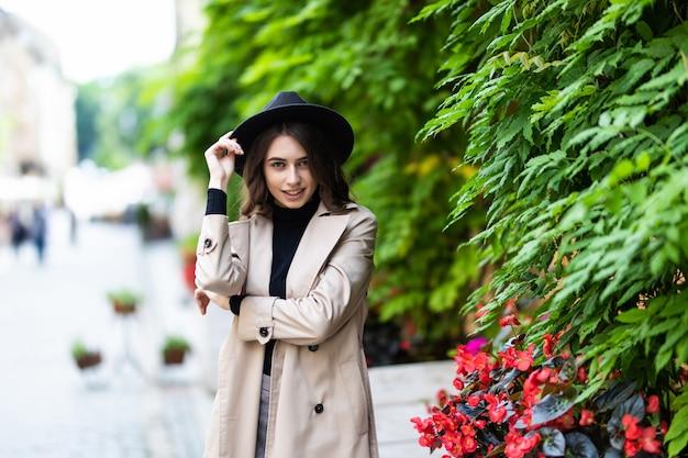Belle jeune femme en chapeau et manteau marchant dans la ville.